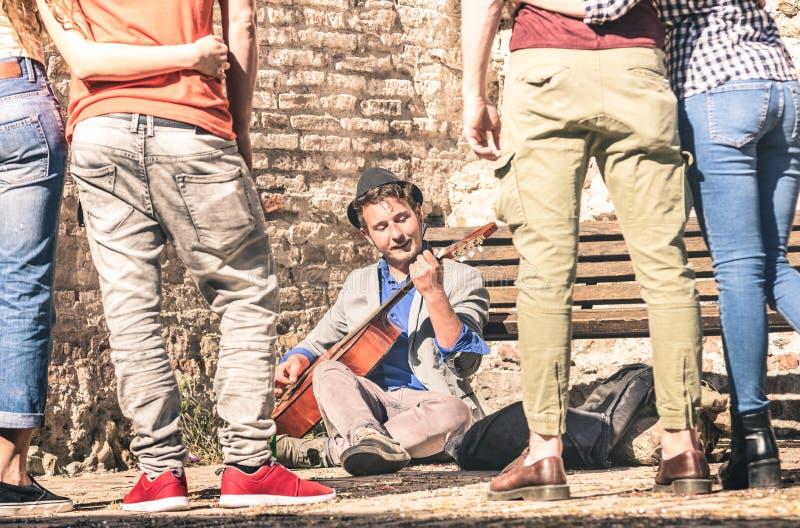 弹吉他的青年人观看的街道艺术家执行者 免版税库存照片