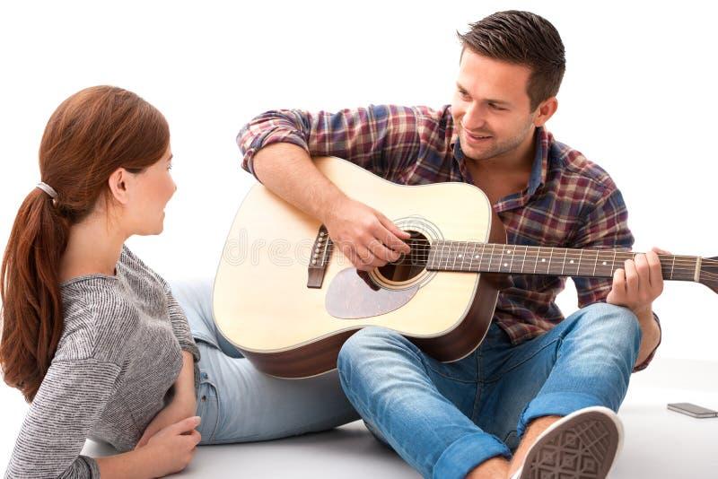 弹吉他的年轻夫妇 免版税库存照片