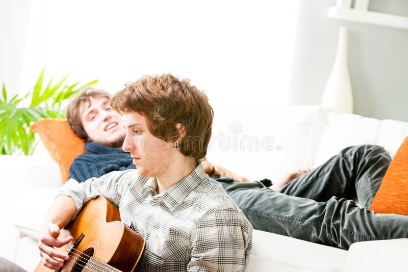 弹在客厅地板上的年轻人吉他 免版税库存照片