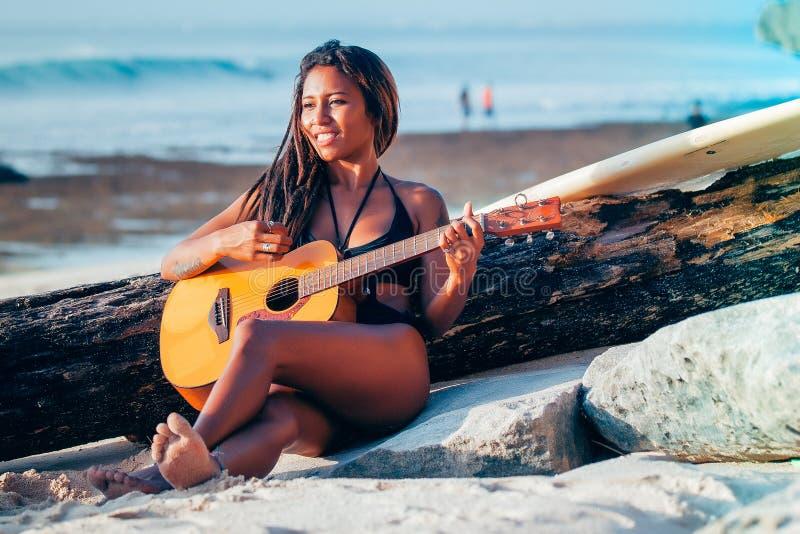 弹在海滩的冲浪者女孩吉他 库存照片