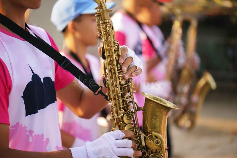 弹在游行乐队声音好听/爵士乐心情的音乐家萨克斯管概念 库存图片