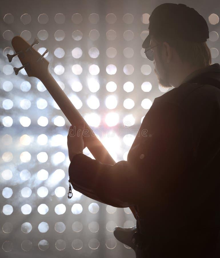 弹在烟的低音歌手低音吉他 免版税图库摄影