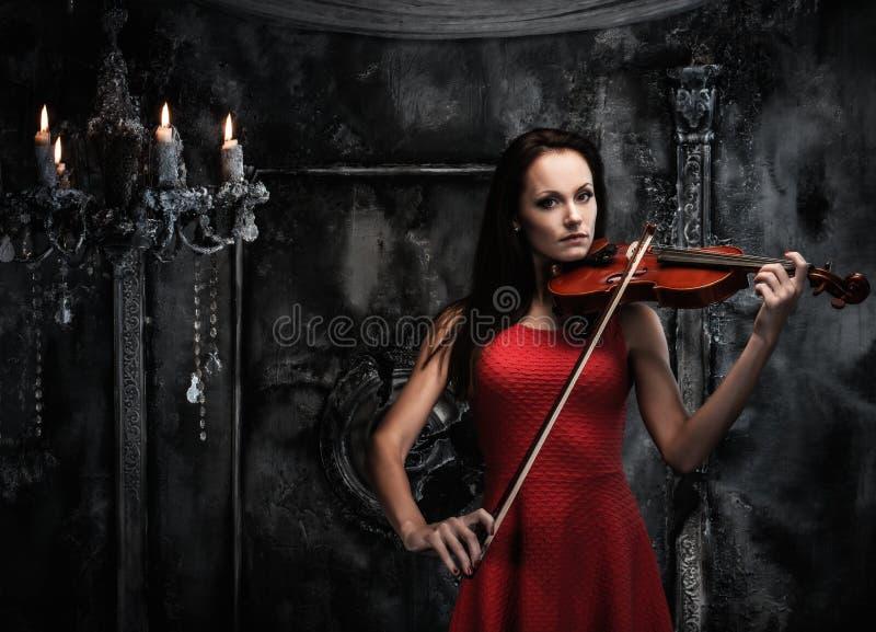 弹在神秘的内部的妇女小提琴 免版税图库摄影