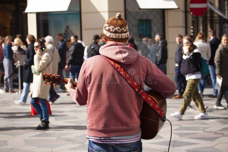 弹在繁忙的走的街道的街道音乐家吉他有走的人的  免版税库存照片