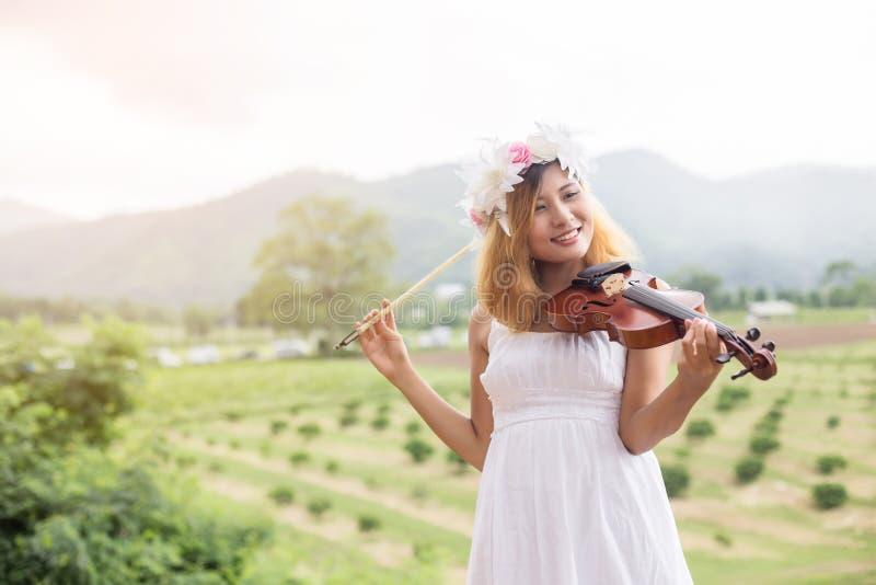 弹在自然室外生活方式的年轻行家音乐家妇女小提琴在山后 库存图片