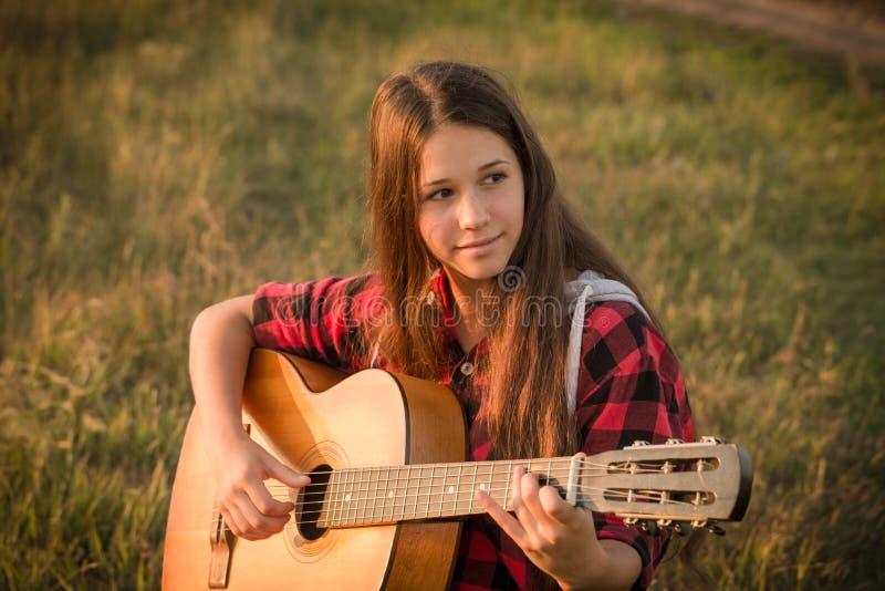 弹在草甸的女孩吉他在日落 免版税库存图片