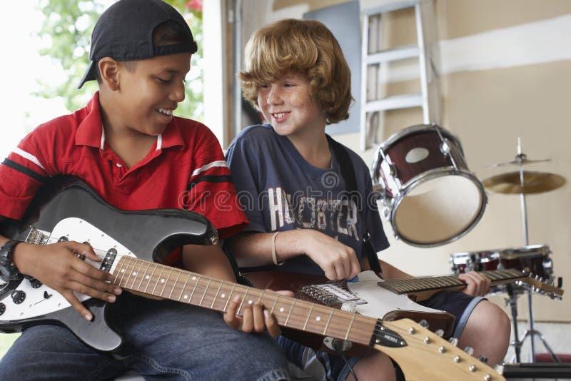 弹在车库的男孩吉他 免版税库存图片