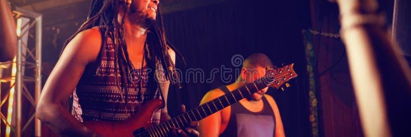 弹在阶段的吉他弹奏者吉他 免版税库存照片
