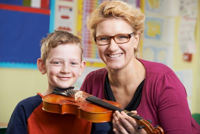 弹在音乐课的小提琴的老师帮助的公学生 图库摄影