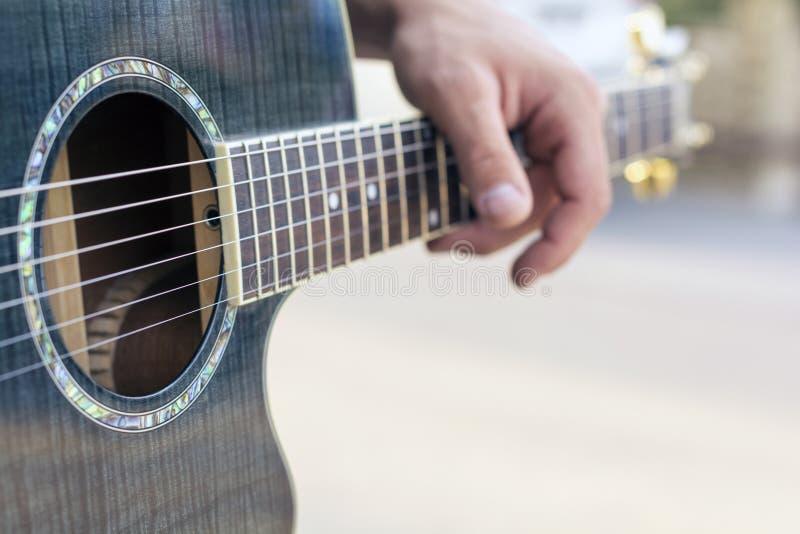 弹声学吉他的接近的手音乐家 库存照片