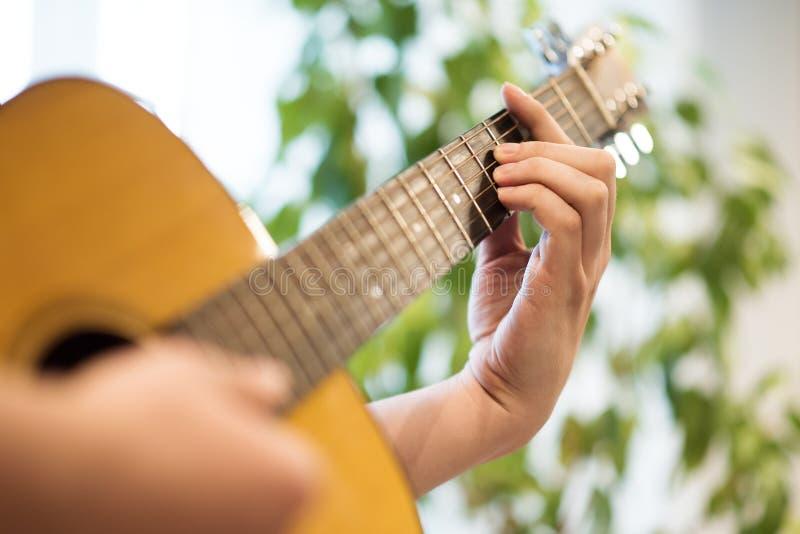 弹声学吉他 在甲板和边缘的男性手 免版税库存照片