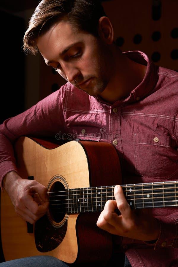 弹声学吉他的人在录音室 免版税库存图片