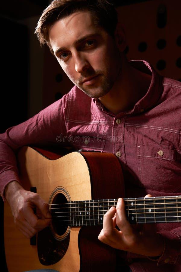 弹声学吉他的人在录音室 库存图片