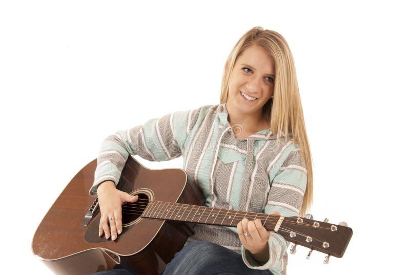 弹声学吉他的年轻白肤金发的妇女 免版税库存照片