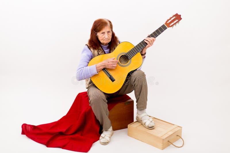 弹声学吉他的滑稽的年长夫人 免版税库存照片