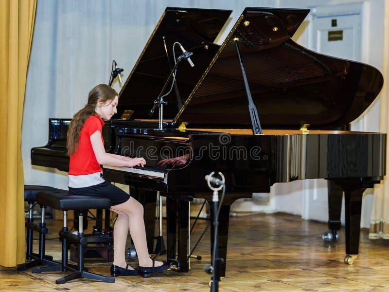 弹大平台钢琴的十几岁的女孩 免版税库存照片