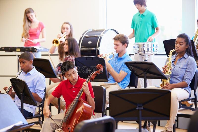 弹奏在学校乐队的学生乐器 图库摄影