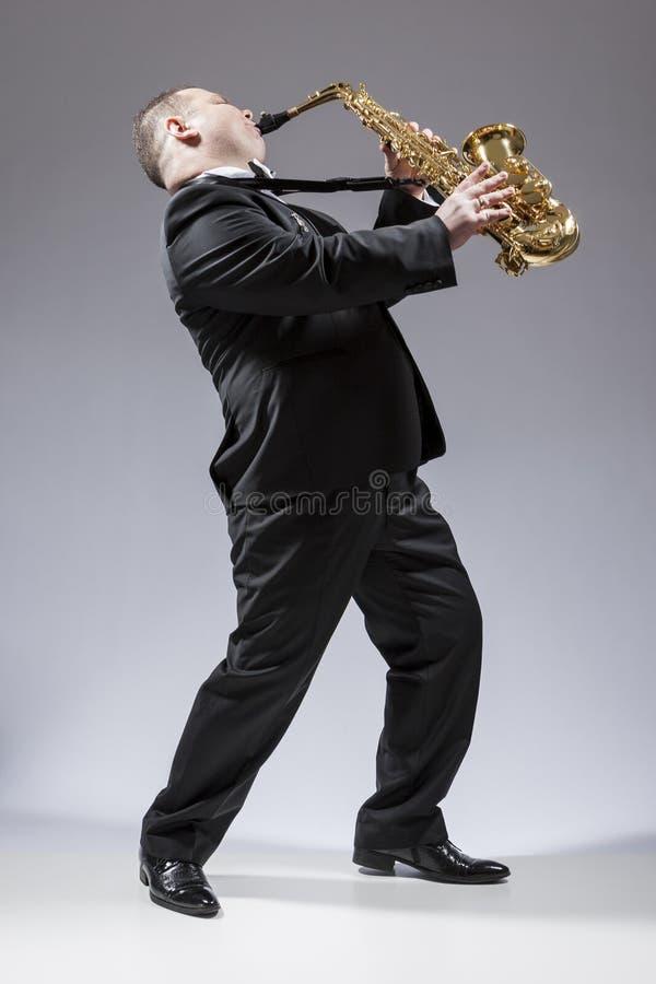 弹奏仪器的白种人成熟传神萨克管演奏员全长画象  免版税图库摄影