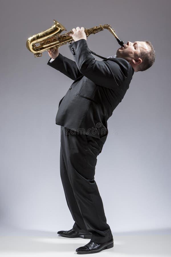 弹奏仪器的白种人成熟传神萨克管演奏员全长画象  库存照片