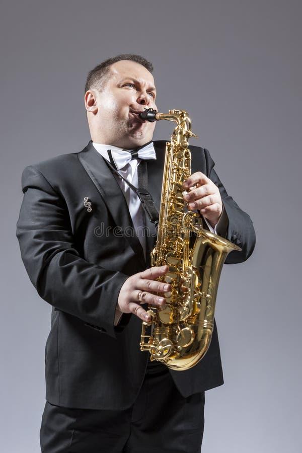 弹奏仪器的白种人成熟传神萨克管演奏员画象  库存图片