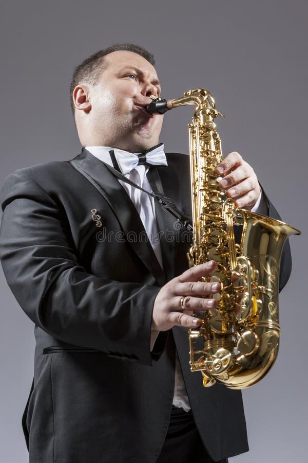 弹奏仪器的白种人成熟传神萨克管演奏员 库存照片