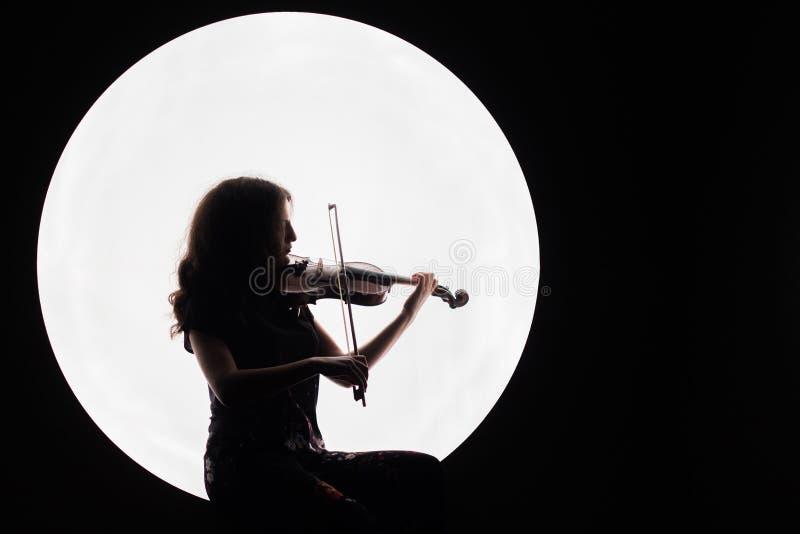弹小提琴的一个美丽的深色的女孩的剪影 音乐新闻的概念 复制空间 白色圈子作为月亮 图库摄影