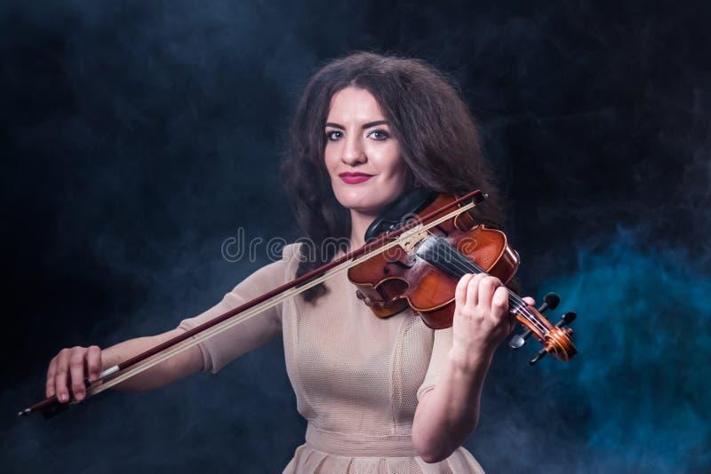 弹小提琴的一件轻的米黄礼服的美丽的深色的女孩 音乐新闻的概念 发烟性的背景 免版税图库摄影