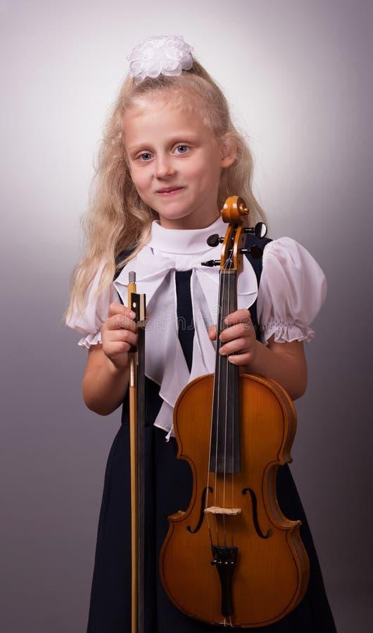 弹小提琴的典雅的衣裳的微笑的女孩 免版税库存图片