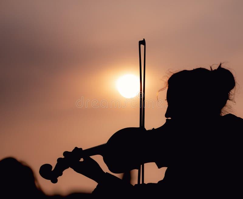 弹小提琴的女性剪影在日落期间反对在布拉格采取的太阳 免版税图库摄影