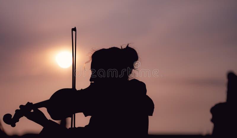 弹小提琴的女性剪影在日落期间反对在布拉格采取的太阳 免版税库存图片