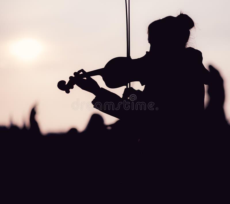 弹小提琴的女性剪影在日落期间反对在布拉格采取的太阳 免版税库存照片