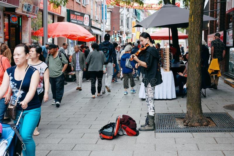 弹小提琴的年轻亚裔女性街道音乐家 免版税库存照片