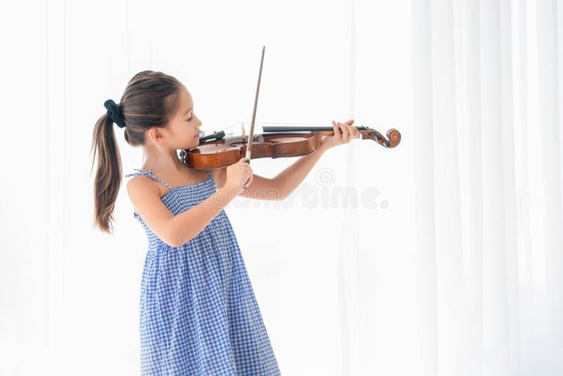 弹小提琴的逗人喜爱的女孩在白色卧室有白色帷幕背景 音乐会和人生活方式 教育和休闲 免版税图库摄影
