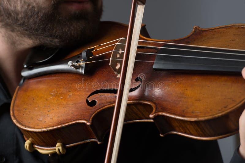 弹小提琴的音乐家人 在执行者的乐器 库存照片