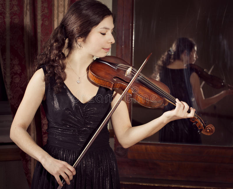 弹小提琴的女孩的画象 免版税库存图片