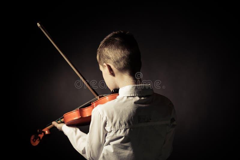 弹小提琴的孩子背面图在变暗的屋子里 免版税图库摄影