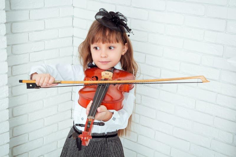 弹小提琴的小女孩 免版税库存照片
