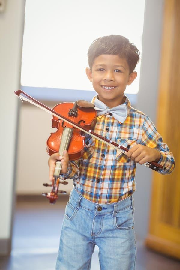 弹小提琴的微笑的男小学生画象 免版税库存图片