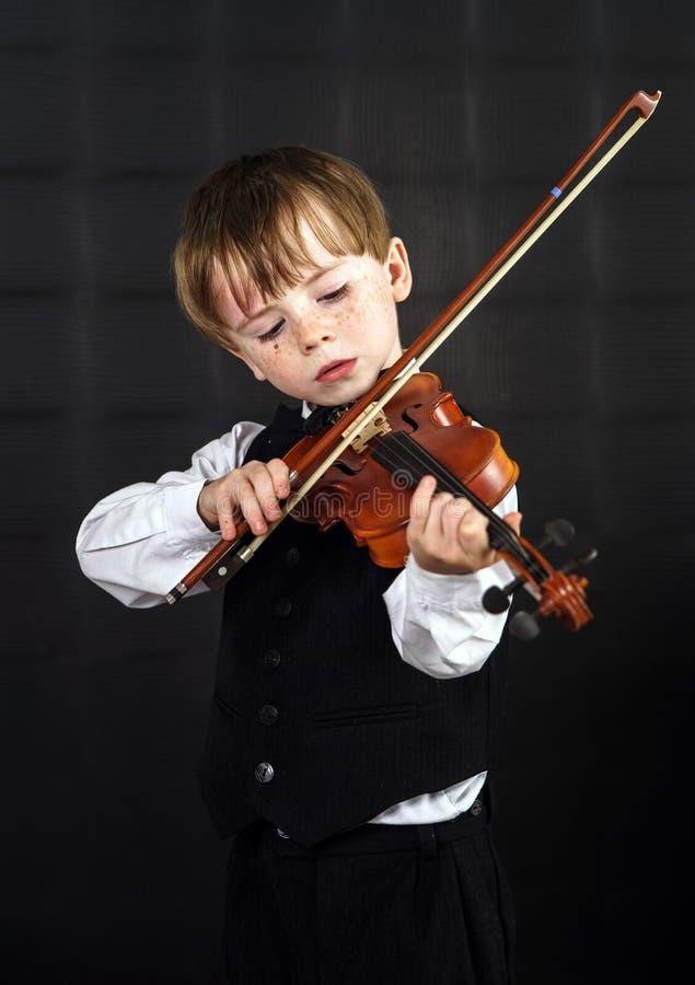 弹小提琴的有雀斑的红头发男孩。 免版税库存照片