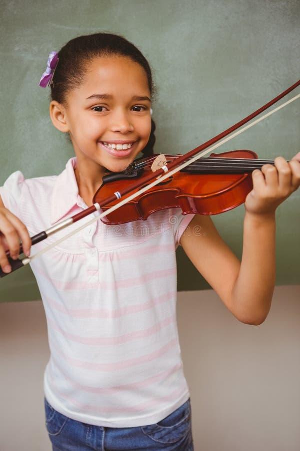 弹小提琴的逗人喜爱的小女孩画象  免版税库存图片