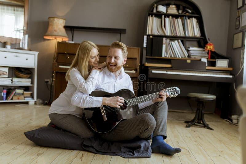 弹年轻美女的人声学吉他 免版税库存图片