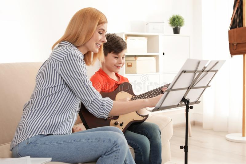 弹有他的老师的小男孩吉他在音乐课 免版税库存图片