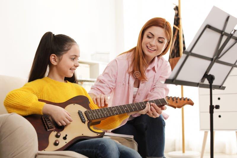 弹有她的老师的女孩吉他在音乐课 免版税图库摄影