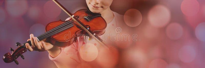 弹有桃红色光的女孩小提琴 库存图片