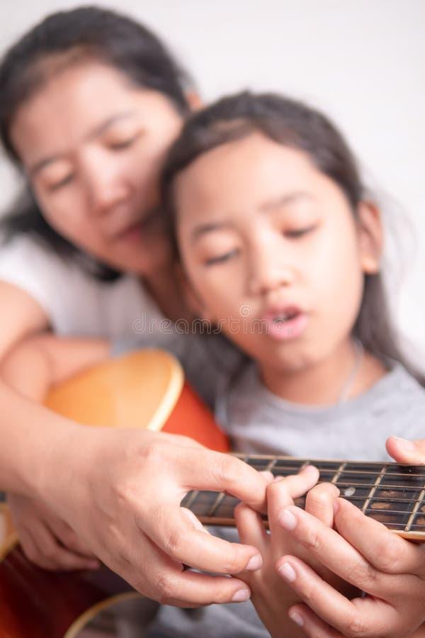 弹有母亲的女孩一把吉他 免版税图库摄影