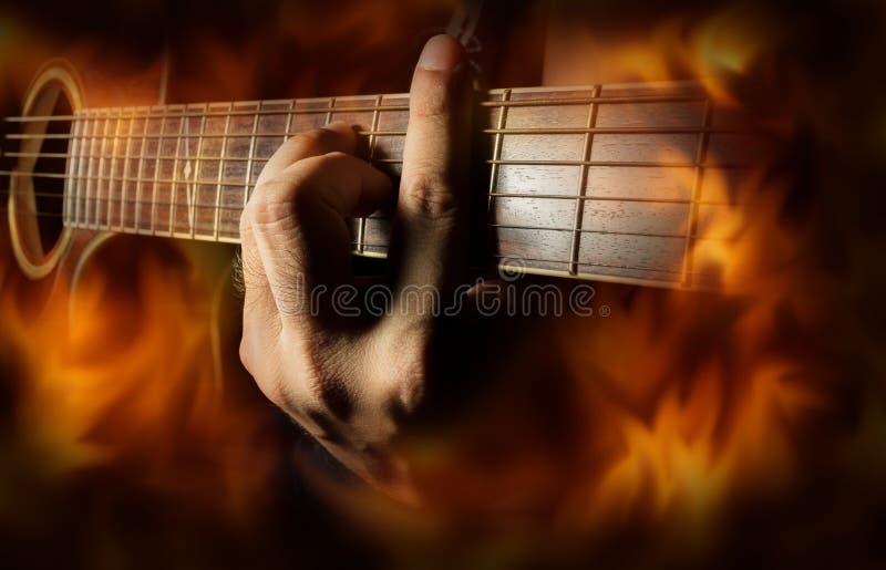 弹有火火焰屏幕的声学吉他 库存图片
