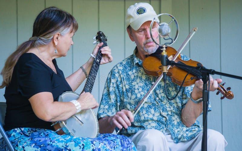 弹班卓琵琶和小提琴的男性和女性 免版税库存照片