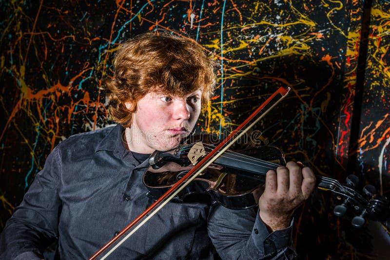 弹用不同的情感o的红发有雀斑的男孩小提琴 免版税库存照片