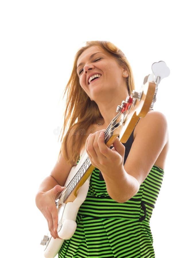弹电低音吉他的绿色礼服的妇女 免版税图库摄影