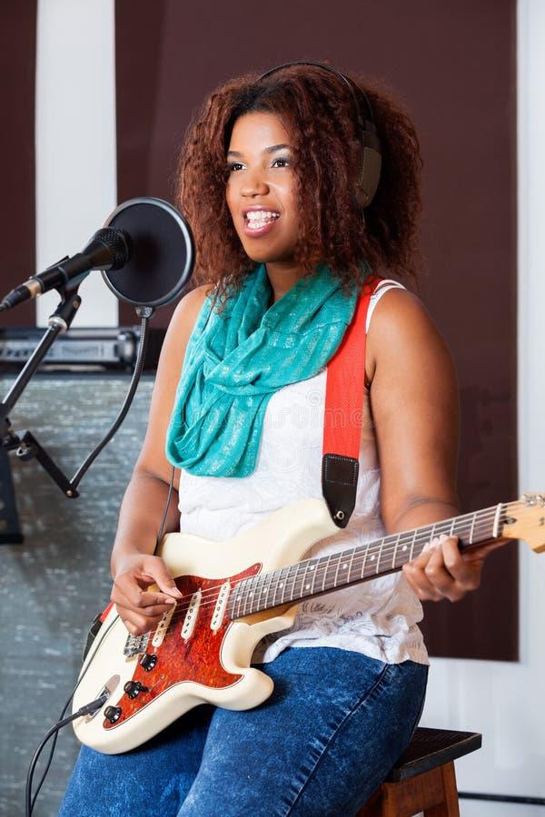弹电吉他的女歌手,当时 图库摄影